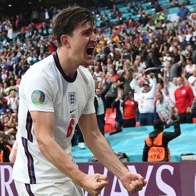 Harry Maguire tuulettaa jalkapallon EM-neljännesvälierässä Saksaa vastaan. Taustalla Wembleyn lehtereillä villiintyneitä kannattajia.