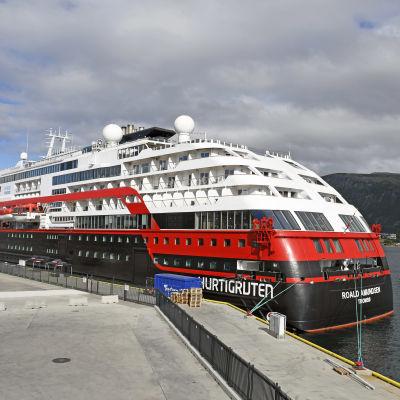 Bild på svart, rött, vitt kryssningsfartyg i hamn. I bakgrunden syns berg.