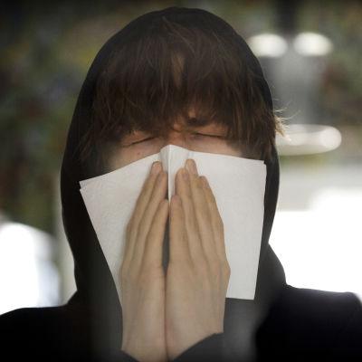 Närbild av ung person i en svart luvtröja. Personen snyter sig i en pappersnäsduk.