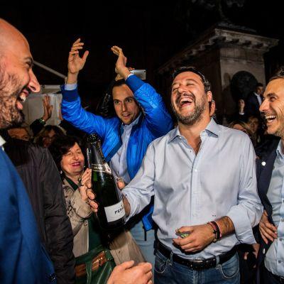Matteo Salvini står med en Champagneflaska i handen och ser strålande glad ut.