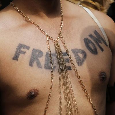 """Miehen paljaaseen rintakehään kirjoitettu sana """"Freedom""""."""