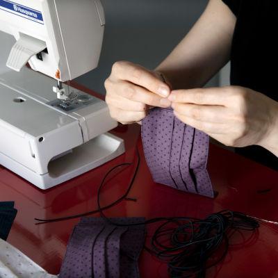 En person syr ett munskydd av tyg. Man ser bara personens händer och symaskinen och tygbiten.