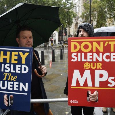 """Två brexit demonstranter håller upp varsin skylt med texterna: """"They misled the queen"""" och """"don't silence ur MPs""""."""