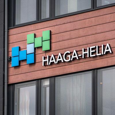 """En televägg och en skylt med texten """"Haaga-Helia"""""""