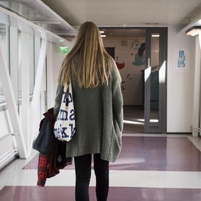 En flicka går i en korridor.