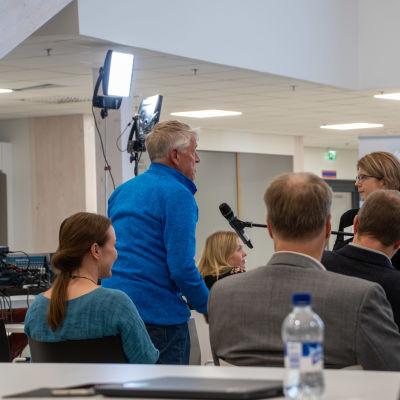 Bengt Gustavsson ställer en fråga på informationstillfället i Lovisavikens skola. På bilden syns Bengt som stpr upp bland publiken och en person som håller en mick framför honom.