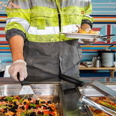 En person i smutsiga arbetskläder tar mat från buffet på lunchrestaurang. Använder engångshandskar.