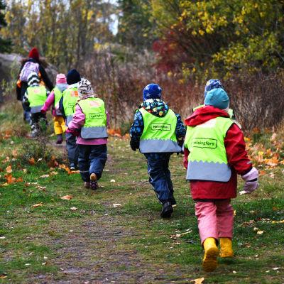 Lapset juoksevat päiväkodissa.