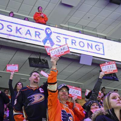 Fans håller upp pappersark för att hylla Oskar Lindblom.