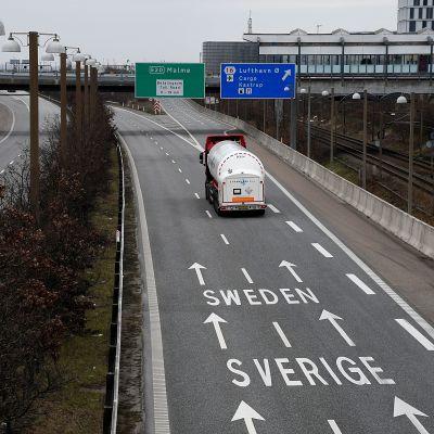 Rekka ajaa pitkin autiota tietä, johon on maalattu nuolia ja Ruotsi-teksti.