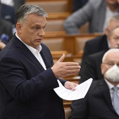 Viktor Orban puhuu paperit kädessään. Taustalla mies hengityssuojuksessa.