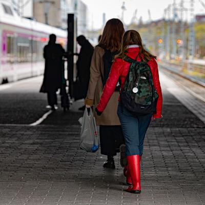 Ihmisiä Helsingin rautatieasemalla menossa paikallisjuniin.