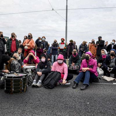 Människor, demonstranter, sitter på Mannerheimvägen.