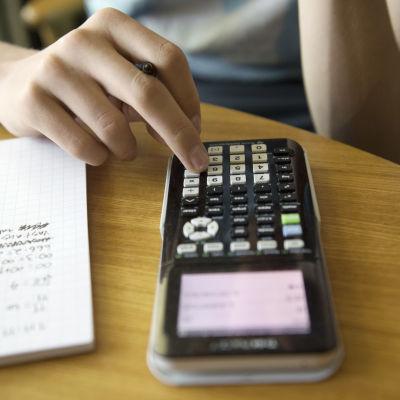 En person som använder en miniräknare.