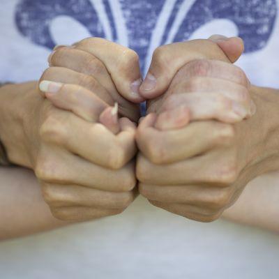 Mies pitelee kahden naisen kättä