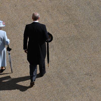 Kuningatar Elisabet ja prinssi Andrew kävelevät rinnakkain hiekkakentällä selät kameraan päin.