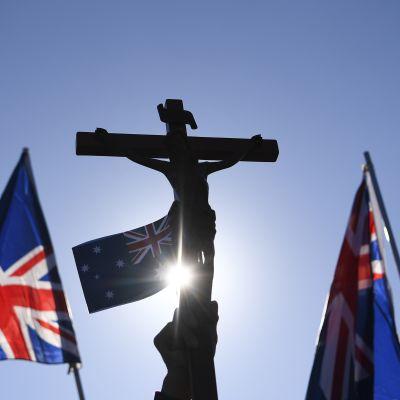 En hand som håller upp ett krucifix och två australiska flaggor