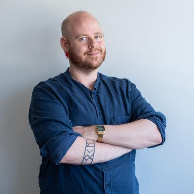 En man med rakad skalle och skägg klädd i kraglös skjorta tittar in i kameran.