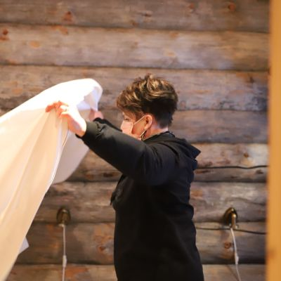 Nainen vaihtaa lakanaa hirsimökissä.