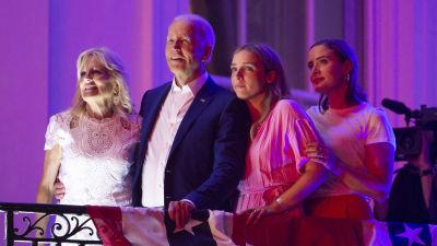 Presidentparet Biden står på en balkong vid Vita huset och väntar på att se fyrverkerier den 4 juli 2021 tillsammans med sina barnbarn.