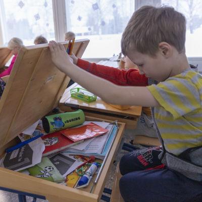 En elev har lyft upp locket till sin pulpet och letar efter material.