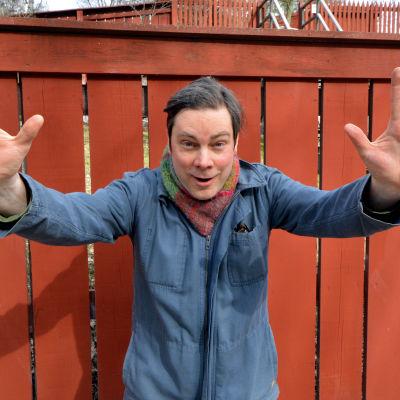 Jukka Rintamäki tittar in i kameran och visar upp sina händer.