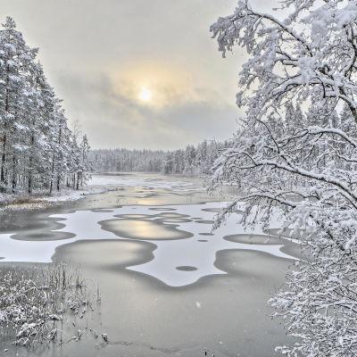 Istäcke över sjö i vintrigt landskap.