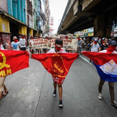 mielenosoittajia kommunistilippujen kanssa