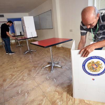 Vaalivirkailija kasaa äänestyskoppia.