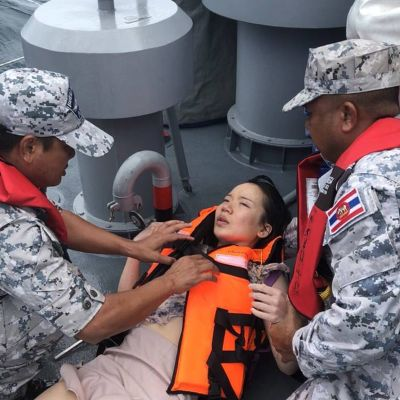 Thailändska marinsoldater hjälper en turist som befann sig ombord på båten som förliste utanför Phukets kust.