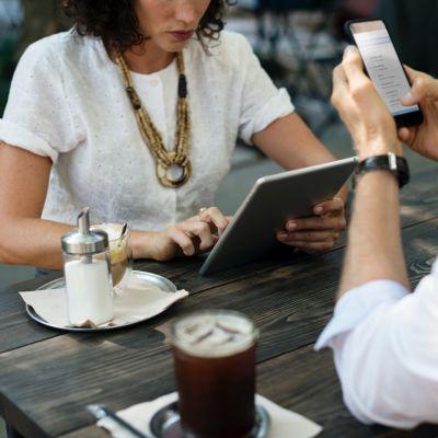 En kvinna och en man siiter vid ett bord och arbetar med en telefon och en pekplatta.