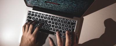 Bilden visar två händer som skriver på en bärbar dator.