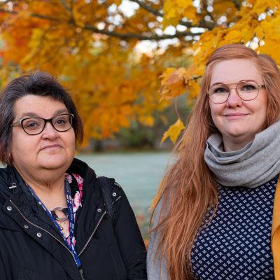 Två kvinnor ser in i kameran. I bakgrunden ett träd med höstgula löv.