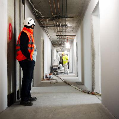 Byggarbetare står i en korridor.