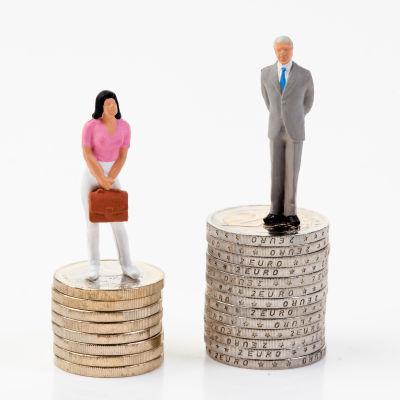 Två högar med mynt, en lägre än den andra. På den lägre bestående av 1-euron står en kvinna, på den högre bestående av 2-euron står en man.