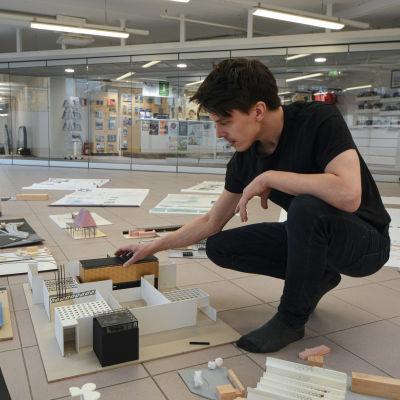 Man sitter på huk och håller i en miniatyrmodell av byggnadsstrukturer.