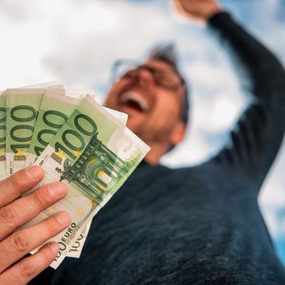 Mies nauraa kädessään setelinippu