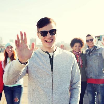 Fem stycken ungdomar står och vinkar mot kameran. Längst fram står en kille med solglasögon.