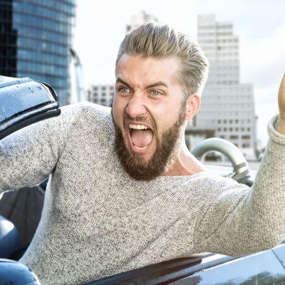 En man som ropar medan han kör bil med höjd arm.
