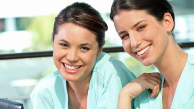 Två leende kvinnor i sjukhuskläder