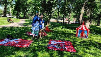 En man och en kvinna utklädda till städerskor står i en lummig park.