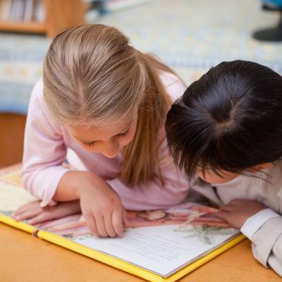 Två flickor läser en bok.