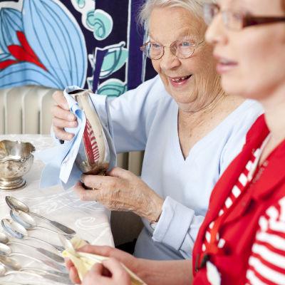 En äldre kvinna som putsar ett silverföremål, en annan kvinna (vårdpersonal) syns i förgrunden.