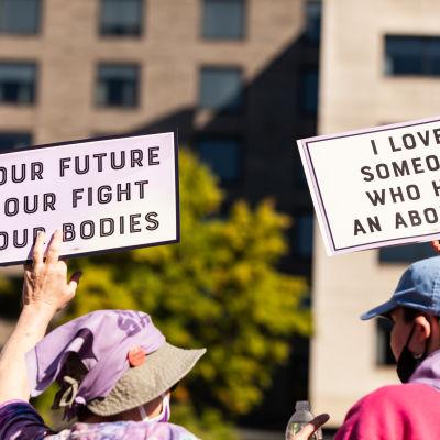 Kaksi mielenosoittajaa ajamassa aborttioikeutta kylttien kanssa.