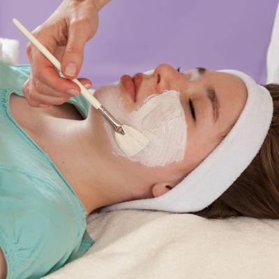 Kosmetologi tekee naiselle kasvohoitoa