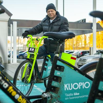Kuopion kaupungin liikkumispalveluiden kehittämispäällikkö Jouni Huhtinen kaupunkipyörän selässä Kuopion-hallin edustalla.