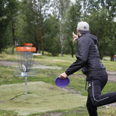 En man kastar en frisbee mot en korg.