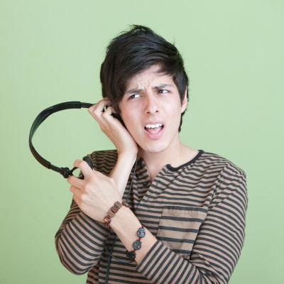 Ung kille som är förbryllad av det han hör i sina hörlurar.