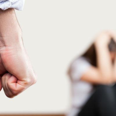 En knuten näve och en person som kurat ihop sig i bakgrunden.
