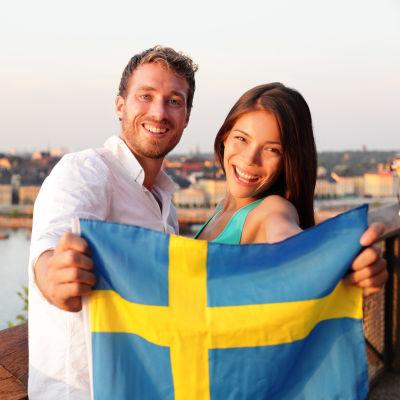 En man och en kvinna håller i en svensk flagga i förgrunden av Stockholm.